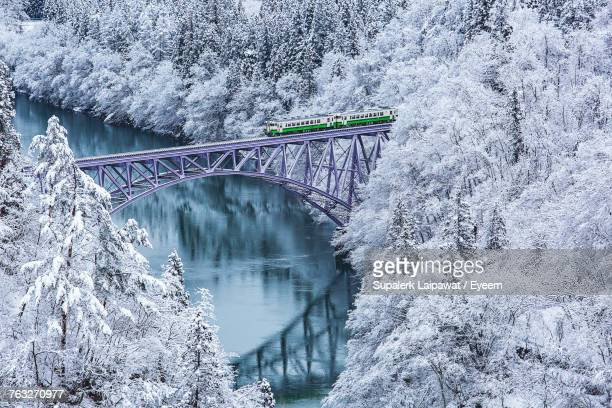 High Angle View Of Train On Bridge Over River Amidst Snow Covered Trees