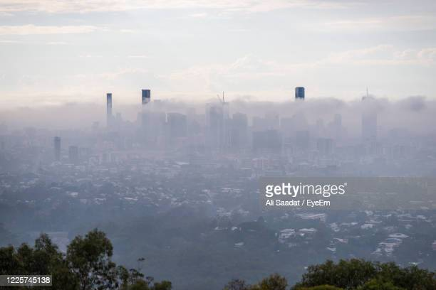 high angle view of trees and buildings in city - smog stock pictures, royalty-free photos & images