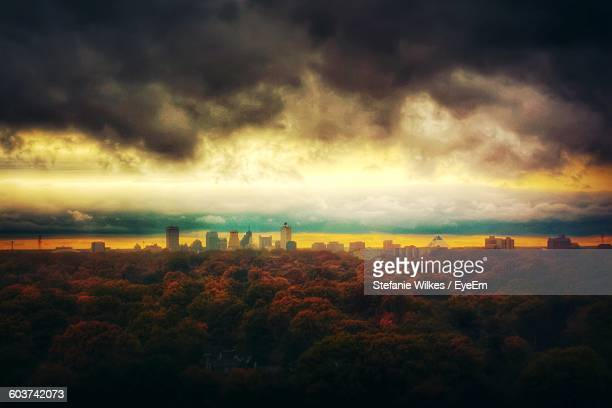 High Angle View Of Trees And City Against Cloudy Sky During Sunset