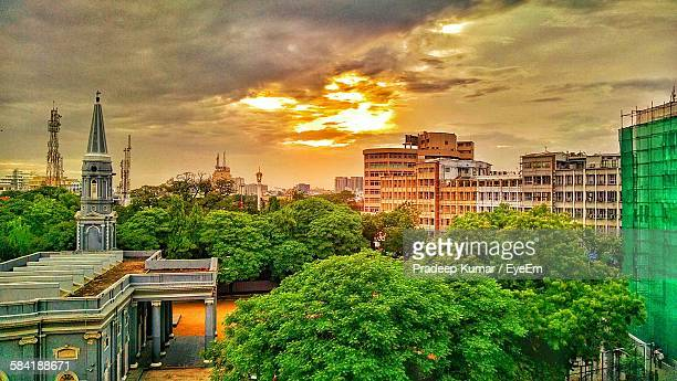 high angle view of trees and cityscape against cloudy sky - chennai stock pictures, royalty-free photos & images