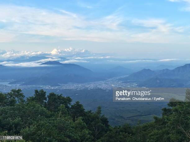 high angle view of trees and mountains against sky - panaikorn chutidaralux stock photos and pictures