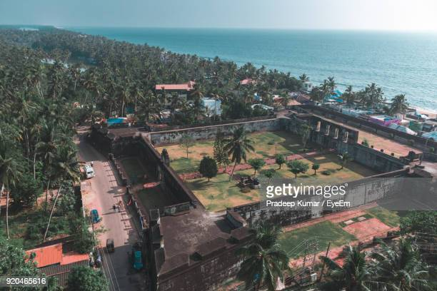 high angle view of trees by sea against clear sky - thiruvananthapuram stock photos and pictures