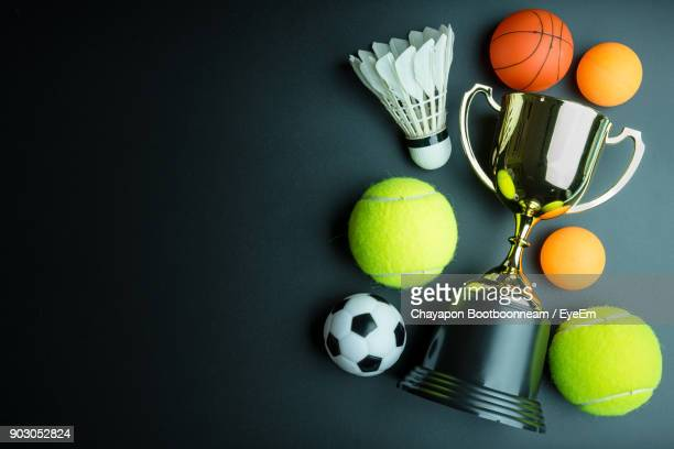 High Angle View Of Trophy With Colorful Balls Over Black Background