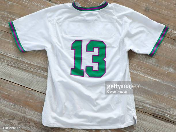 high angle view of t-shirt with number 13 on wooden table - ユニフォーム ストックフォトと画像