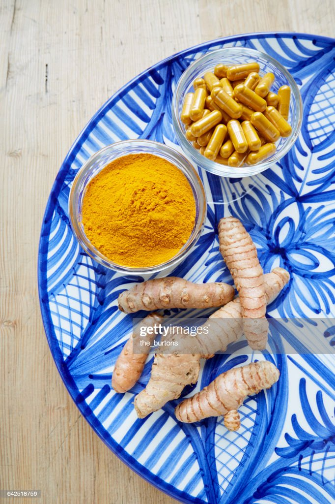 High Angle View Of Turmeric Root Powder And Pills On Plate
