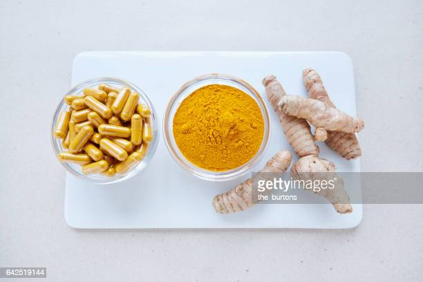 High angle view of turmeric root, powder and pills on white plate