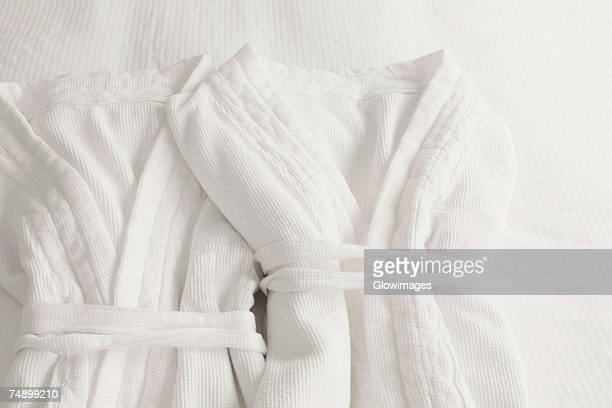 high angle view of two bathrobes on the bed - bathrobe stock pictures, royalty-free photos & images