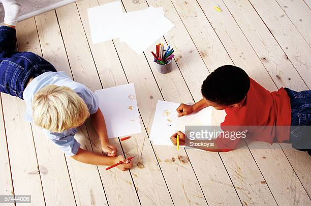high angle view of two boys (8-10) lying on the floor, drawing