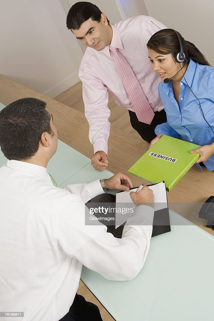 High angle view of two businessmen and a businesswoman talking : Stock Photo