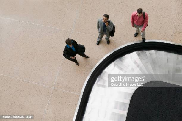 high angle view of two businessmen and one businesswoman standing at a conveyor belt in an airport - baggage claim stock pictures, royalty-free photos & images