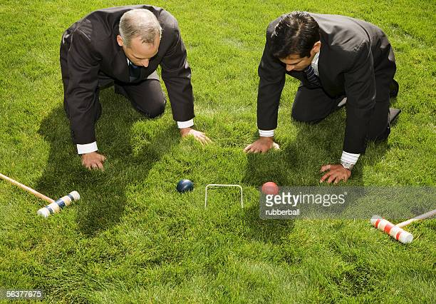 high angle view of two businessmen playing croquet - ひざまずく ストックフォトと画像