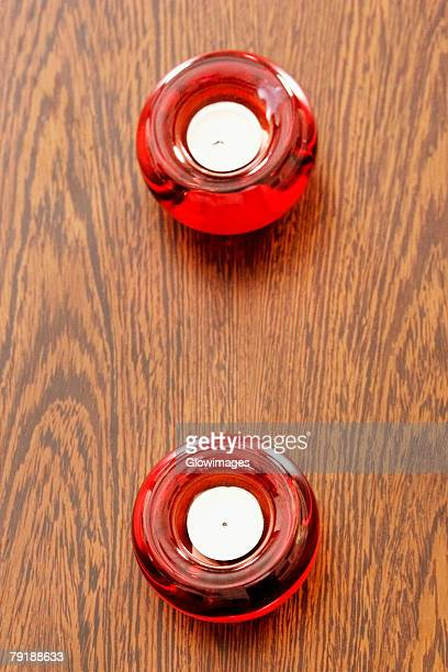 High angle view of two candles in candlestick holders on a table