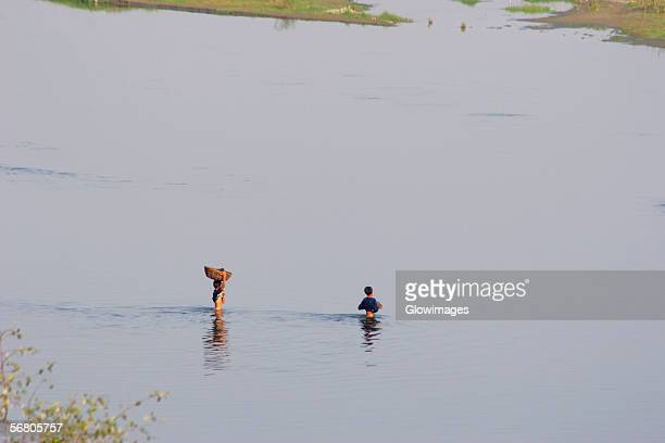 High angle view of two farmers crossing a river, Agra, Uttar Pradesh, India