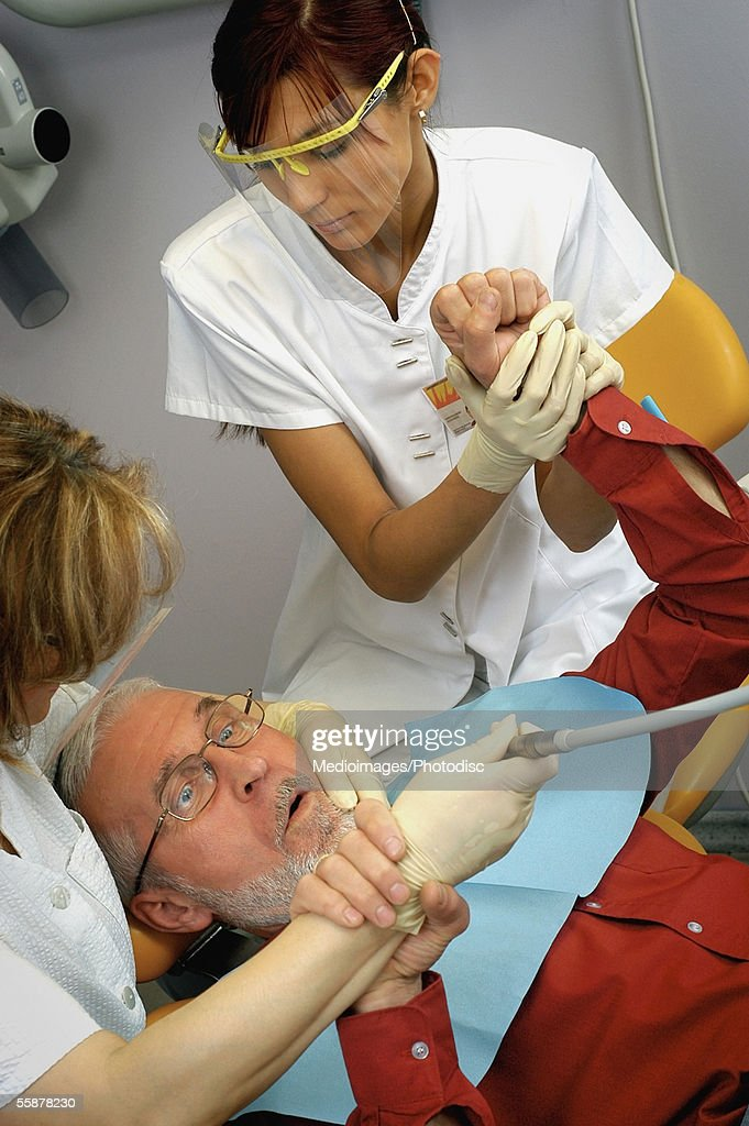 High Angle View Of Two Female Dentists Attending A Scared Male Patient Stock Photo
