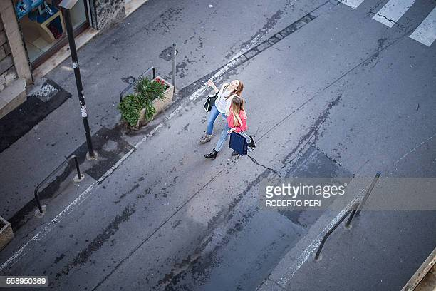 High angle view of two female friends laughing whilst strolling on city street