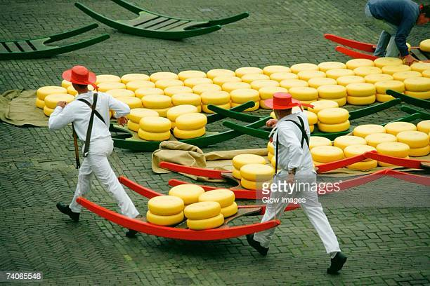 high angle view of two men carrying cheese, alkmaar cheese market, alkmaar, netherlands - cultura holandesa - fotografias e filmes do acervo