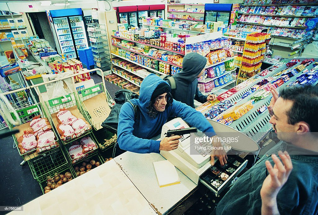 High Angle View of Two Robbers Robbing a Cash Till and Threatening a Shop Assistant with a Gun : Stock Photo