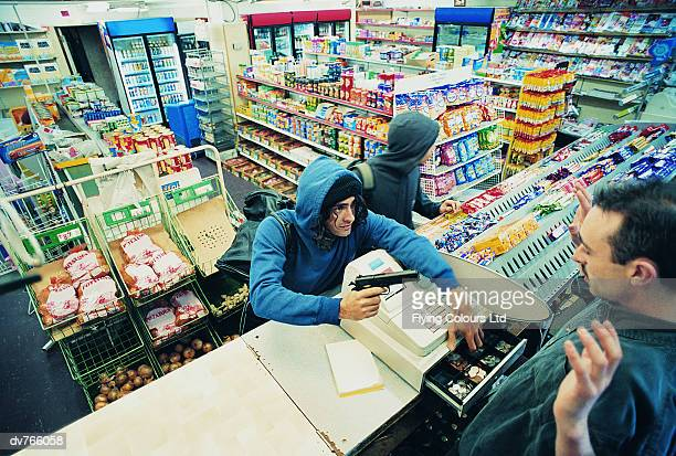 high angle view of two robbers robbing a cash till and threatening a shop assistant with a gun - convenience store stock photos and pictures