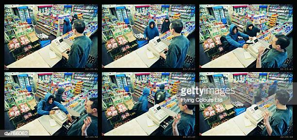 high angle view of two robbers robbing a cash till and threatening a shop assistant with a gun - convenience store counter stock photos and pictures