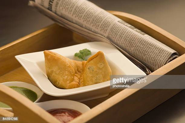 High angle view of two samosas with sauce and a newspaper in a tray
