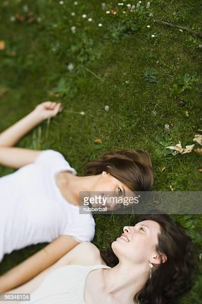 High angle view of two teenage girls lying on grass