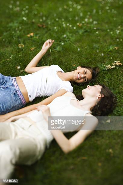 High angle view of two teenage girls lying on the grass