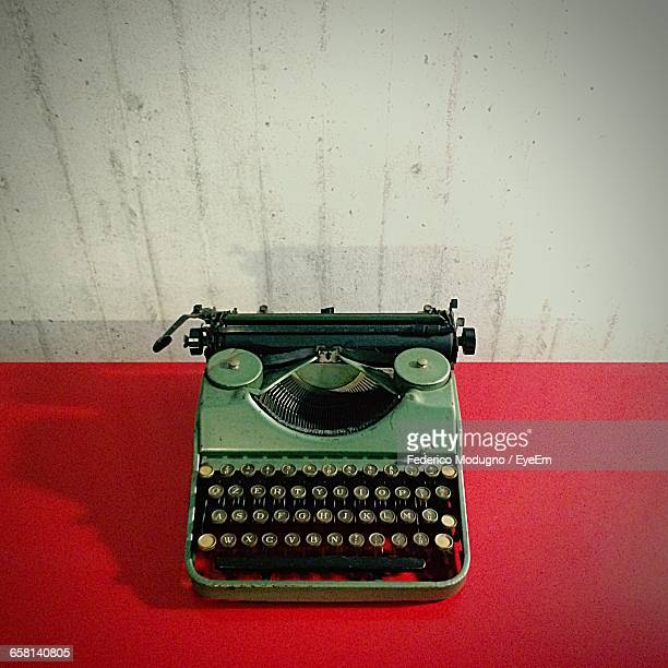 High Angle View Of Typewriter On Red Table Against Wall