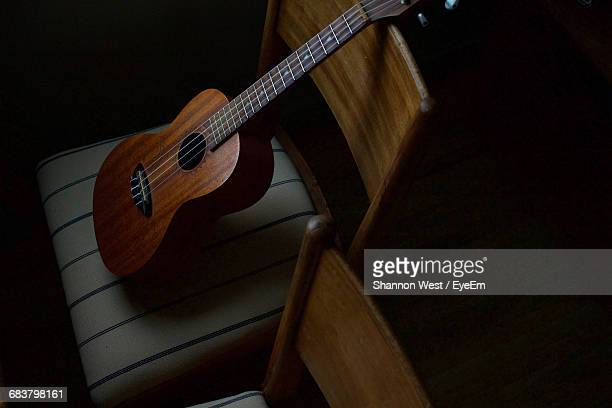 high angle view of ukelele on chair in darkroom - ukulele stock pictures, royalty-free photos & images