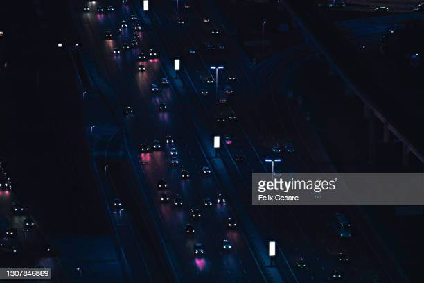 high angle view of urban highway lit up in neon lights during the night. - green car crash stock pictures, royalty-free photos & images