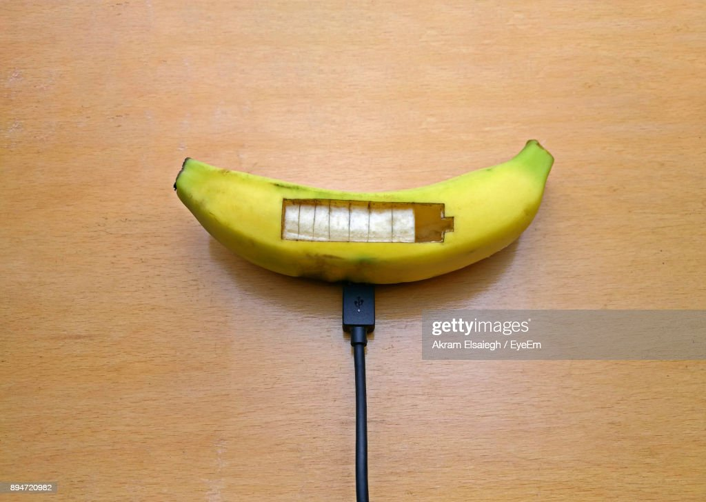 Banana On Table High Angle View Of Usb Cable Connected To Banana On Table : Stock Photo
