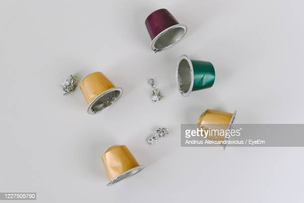 high angle view of used coffee capsules on table against white background - capsule stock pictures, royalty-free photos & images