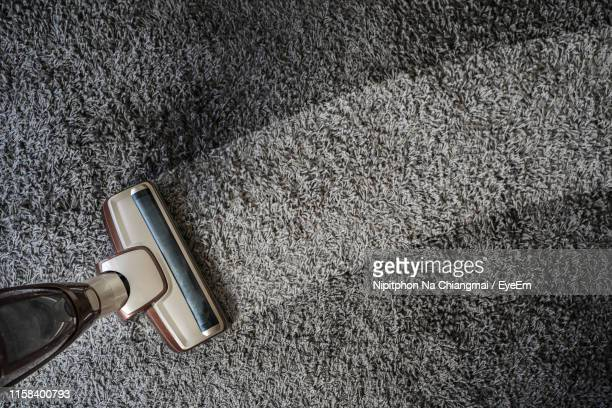 high angle view of vacuum cleaner cleaning carpet at home - カーペット ストックフォトと画像