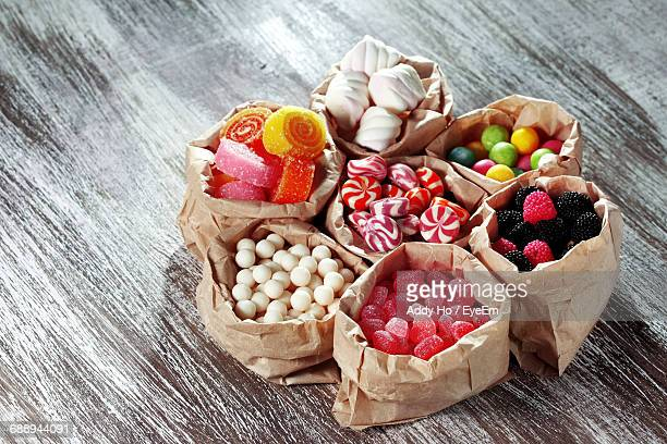 High Angle View Of Various Candies In Paper Bags On Table