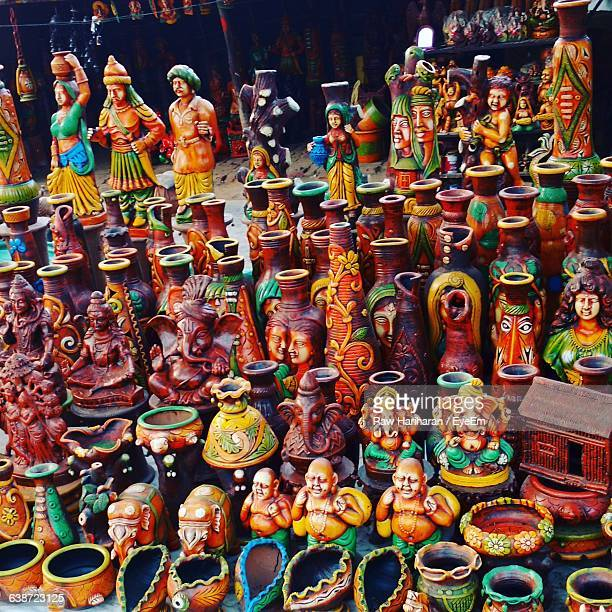 High Angle View Of Various Figurines Displayed At Market Stall