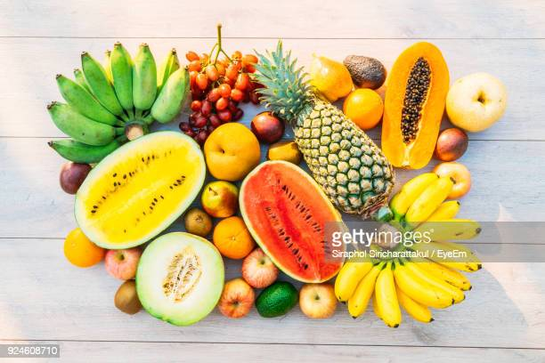 high angle view of various fruits on table - tropische frucht stock-fotos und bilder