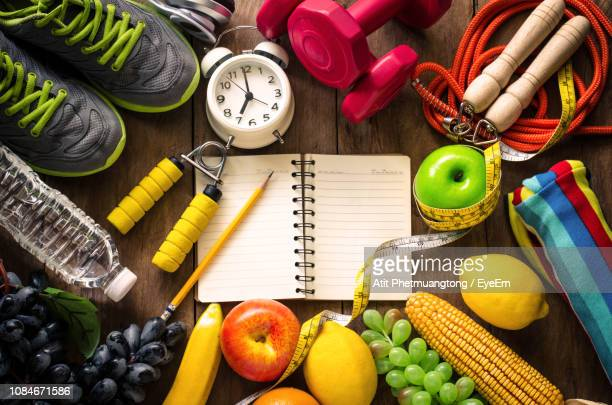 high angle view of various fruits with exercise equipment on table - wellbeing stock pictures, royalty-free photos & images