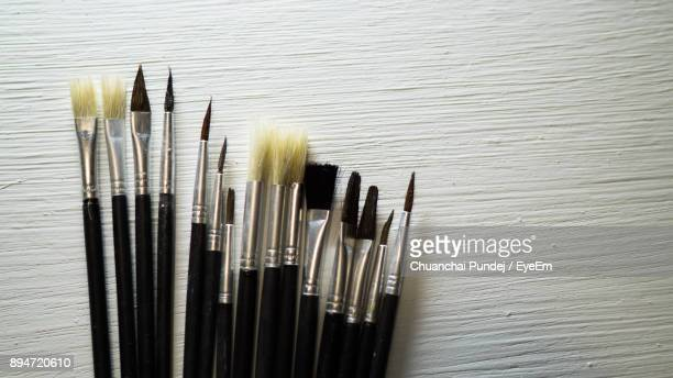 High Angle View Of Various Paintbrushes On Table
