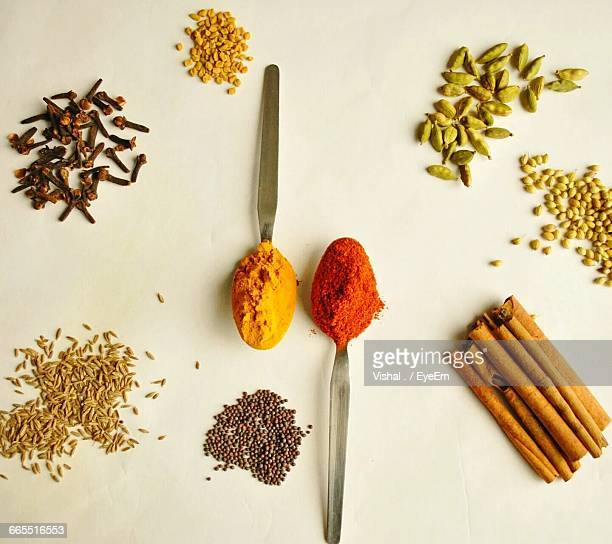 High Angle View Of Various Spices On Table With Spoons