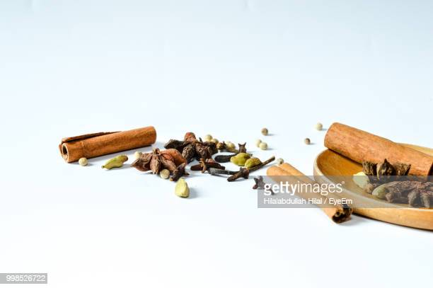 high angle view of various spices on white background - cardamom stock photos and pictures