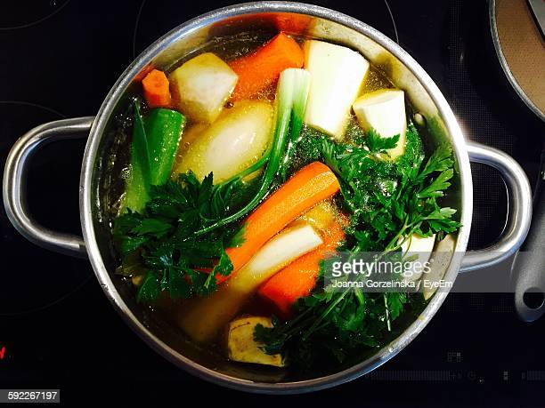 high angle view of vegetables boiling in container - chicken soup stock photos and pictures