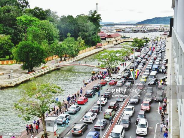 high angle view of vehicles on road by river in city - brunei stock pictures, royalty-free photos & images