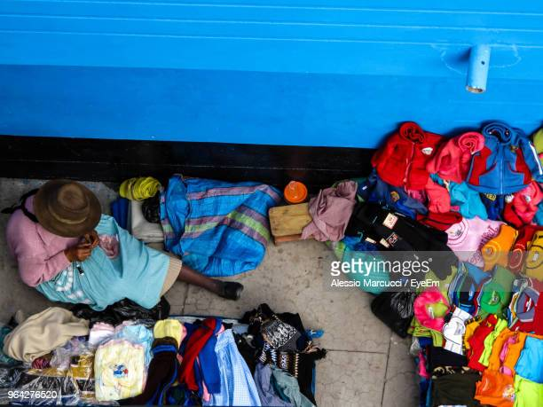 High Angle View Of Vendor Sitting By Market Stall