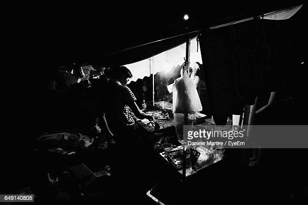 high angle view of vendor standing in street restaurant at night - one night stand stock-fotos und bilder
