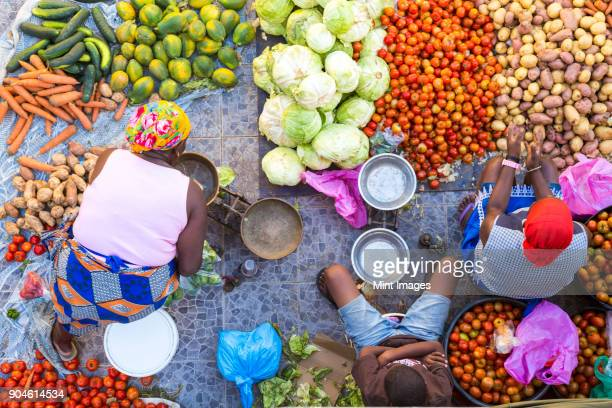 high angle view of vendors selling a selection of fresh vegetables on a street market. - áfrica del oeste fotografías e imágenes de stock