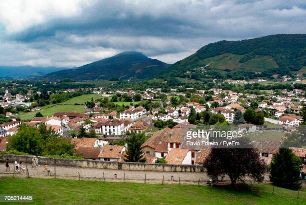 high angle view of village and mountains against sky - saint jean pied de port stock photos and pictures