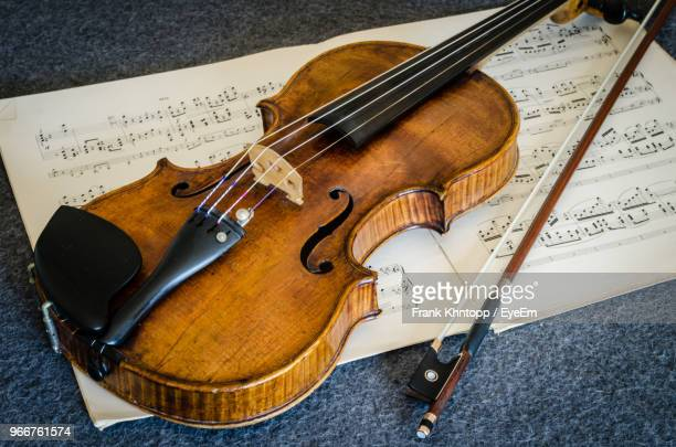 high angle view of violin and sheet music on table - violin stock pictures, royalty-free photos & images