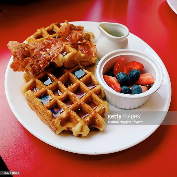 High Angle View Of Waffles And Bacon With Fruits In Plate