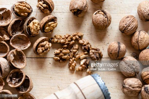 high angle view of walnuts on table - walnut stock pictures, royalty-free photos & images