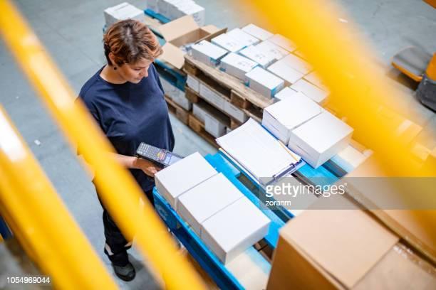 erhöhte ansicht der lagermitarbeiter mit barcode-leser für das scannen von informationen - strichkodeleser stock-fotos und bilder