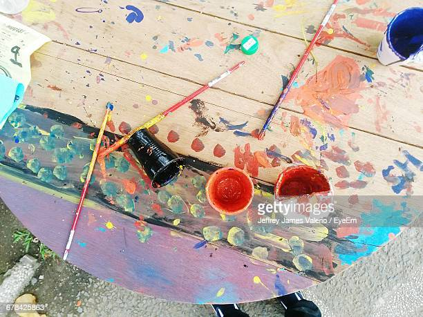 High Angle View Of Watercolor Paints And Brush On Table